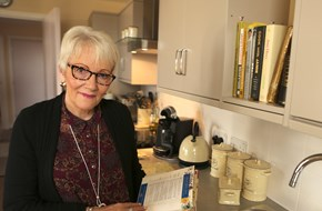 Mature woman in a kitchen holding a cookbook