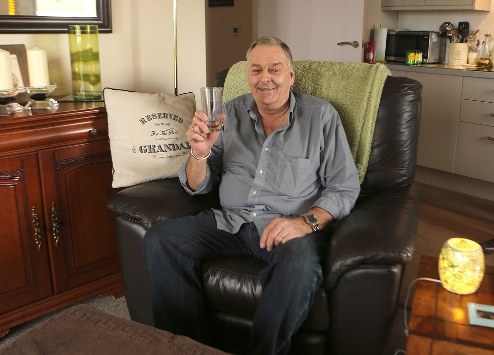 Smiling man sitting in a leather arm chair holding a beer glass