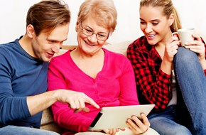 Mature mother sitting on a sofa with older son and daughter smiling looking at a tablet together