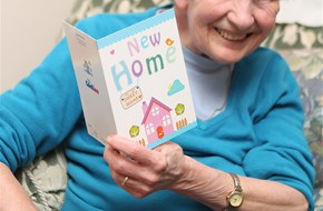 Woman holding a greeting card saying new home