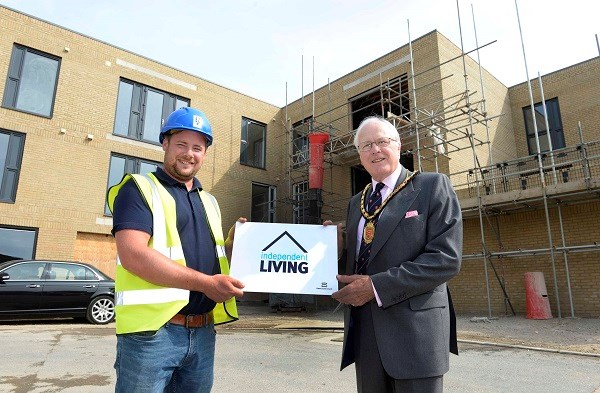 An Essex mayor and building contractor hold Independent Living sign